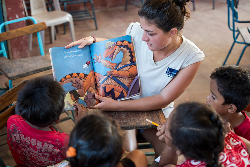 Volunteer helps children learn to read.