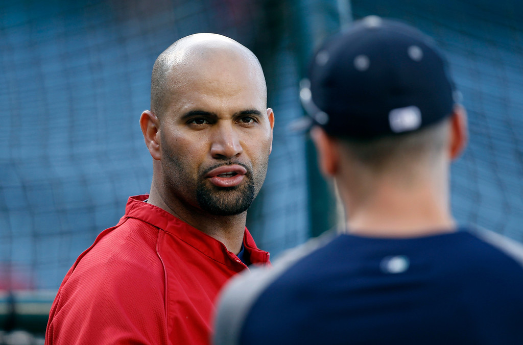 . Los Angeles Angels designated hitter Albert Pujols, left, talks with a Seattle Mariner during batting practice prior to a baseball game Tuesday, May 21, 2013 in Anaheim.    (AP Photo/Alex Gallardo)