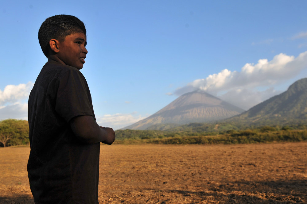 . A stands in a field in Grecia 4, Chinandega, 150 km from Managua, with the San Cristobal volcano in the background on December 26, 2012. The San Cristobal volcano began spewing smoke and ashes Tuesday afternoon. HECTOR RETAMAL/AFP/Getty Images