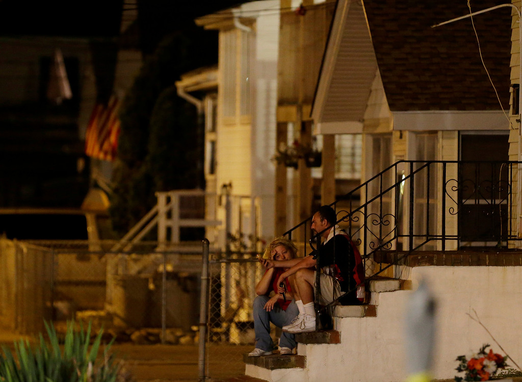 . People sit on the steps of a home near the Seaside Park boardwalk, where earlier in the day a massive fire engulfed businesses on the boardwalk, Thursday, Sept. 12, 2013, in Seaside Park, N.J. The fire, which apparently started near an ice cream shop and spread several blocks, hit the recently repaired boardwalk, which was damaged last year by Superstorm Sandy. There were no other early reports of any injuries. (AP Photo/Julio Cortez)