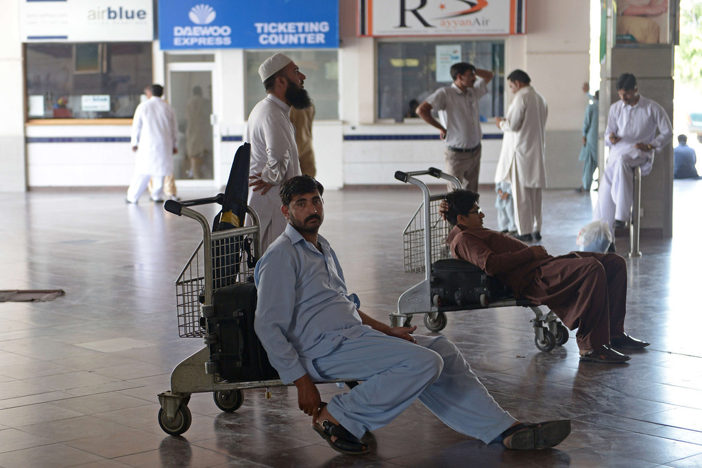 . Passengers of Karachi-bound Pakistan International Airline (PIA) flights wait after delays at the Benazir Bhutto International Airport in Islamabad on June 9, 2014 following gunbattles in Karachi airport between militants and security forces.  AFP PHOTO/Farooq NAEEM/AFP/Getty Images