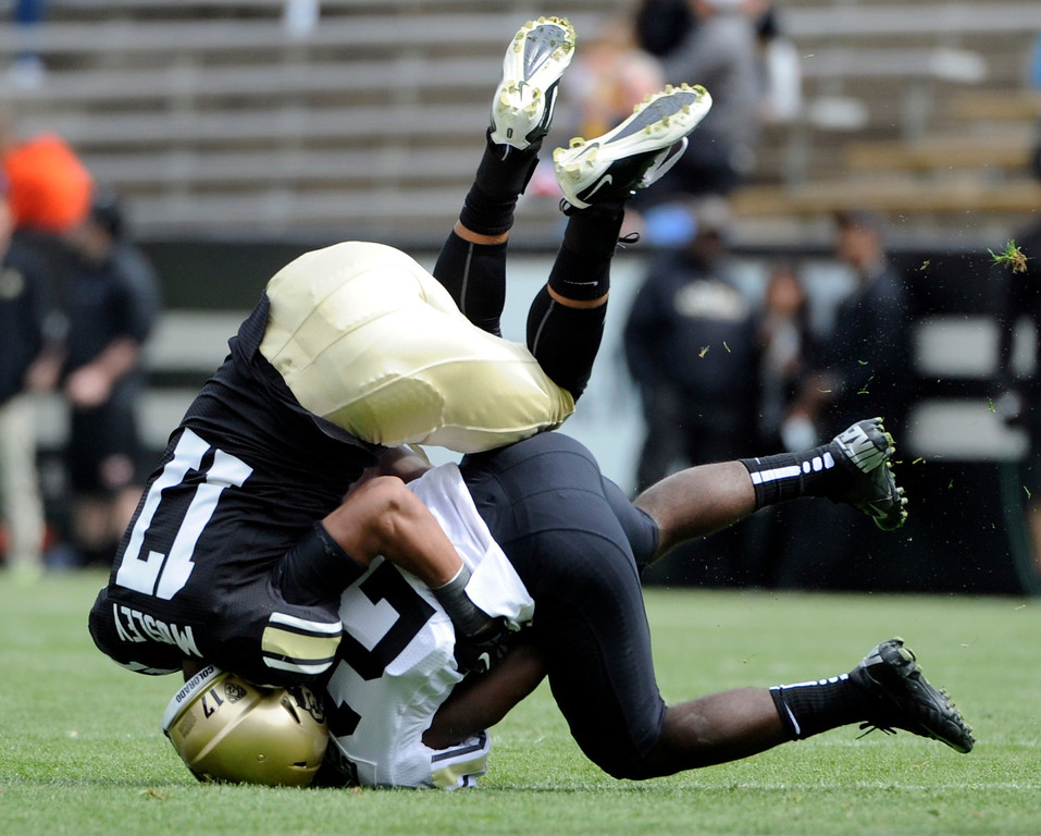 . BOULDER, CO.- APRIL13: Marques Mosley, left, takes down D.D.Goodson but Goodson is able to hang on to the ball. The University of Colorado football team hosts its spring football game at Folsom Field under the direction of new head coach Mike MacIntyre. (Photo By Kathryn Scott Osler/The Denver Post)