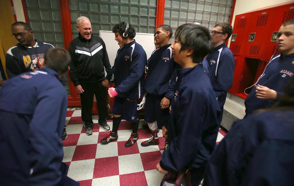 . Albany High School wrestling coach Kermit Bankson, left, center, and assistant coach Tyrone Rose, left, gives their team a pep talk in the locker room before they compete against Tennyson High School in Albany, Calif. on Friday, Jan. 17, 2013. (Jane Tyska/Staff)
