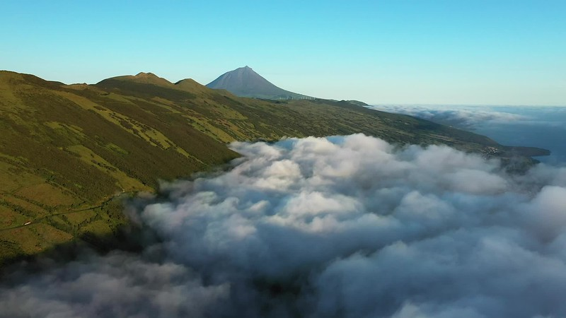 Available in 4K - Aerial video clip of low clouds at sunrise at Pico Island with mount Pico in the background, The Azores