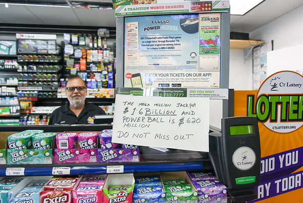 10/22/18 Wesley Bunnell | Staff Manager Iqbal Khan of Sunoco Gas Station at 737 West Main St stands behind the counter after hanging a sign up for customers showing over 2 billion dollars in lottery prize money.