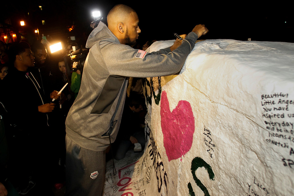 ". MSU basketball player Adreian Payne leaves a message for Lacey Holsworth on Wednesday night, April 9, 2014, in East Lansing, Mich., where he and other people gathered along the banks of the Red Cedar River on the campus of Michigan State University. The little girl affectionately known as ""Princess Lacey\"" finally succumbed to the cancer that she battled since 2011.  Her father, Matt Holsworth, said Lacey died at their home late Tuesday \""with her mommy and daddy holding her in their arms.\"" Lacey met Payne during one of her hospital stays, and their friendship quickly blossomed. The little girl became known to legions of basketball fans, cheering on Payne and the Spartans on Twitter as they became a popular pick to win it all this season. (AP Photo/Lansing State Journal, Matthew Dae Smith) NO SALES"