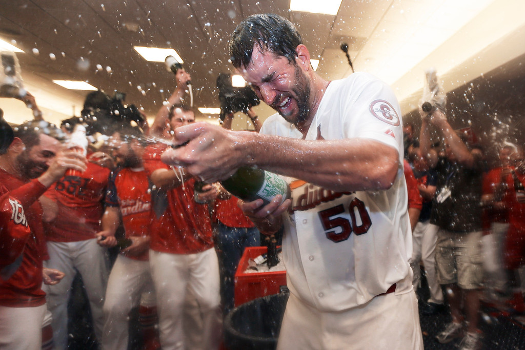 . St. Louis Cardinals pitcher Adam Wainwright (50) and teammates celebrate in the locker room after the Cardinals defeated the Pittsburgh Pirates to win Game 5 in a National League baseball division series, Wednesday, Oct. 9, 2013, in St. Louis. The Cardinals won 6-1, and advanced to the NL championship series against the Los Angeles Dodgers. (AP Photo/Jeff Roberson)