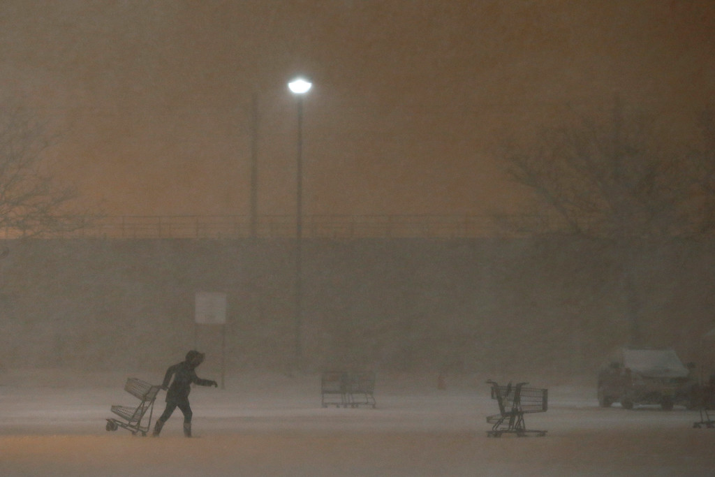 . A grocery store employee collects shopping carts from a parking lot during a snowstorm, Saturday, Jan. 23, 2016, in Jersey City, N.J. Towns across the state are hunkering down during the major snowstorm that hit overnight. (AP Photo/Julio Cortez)