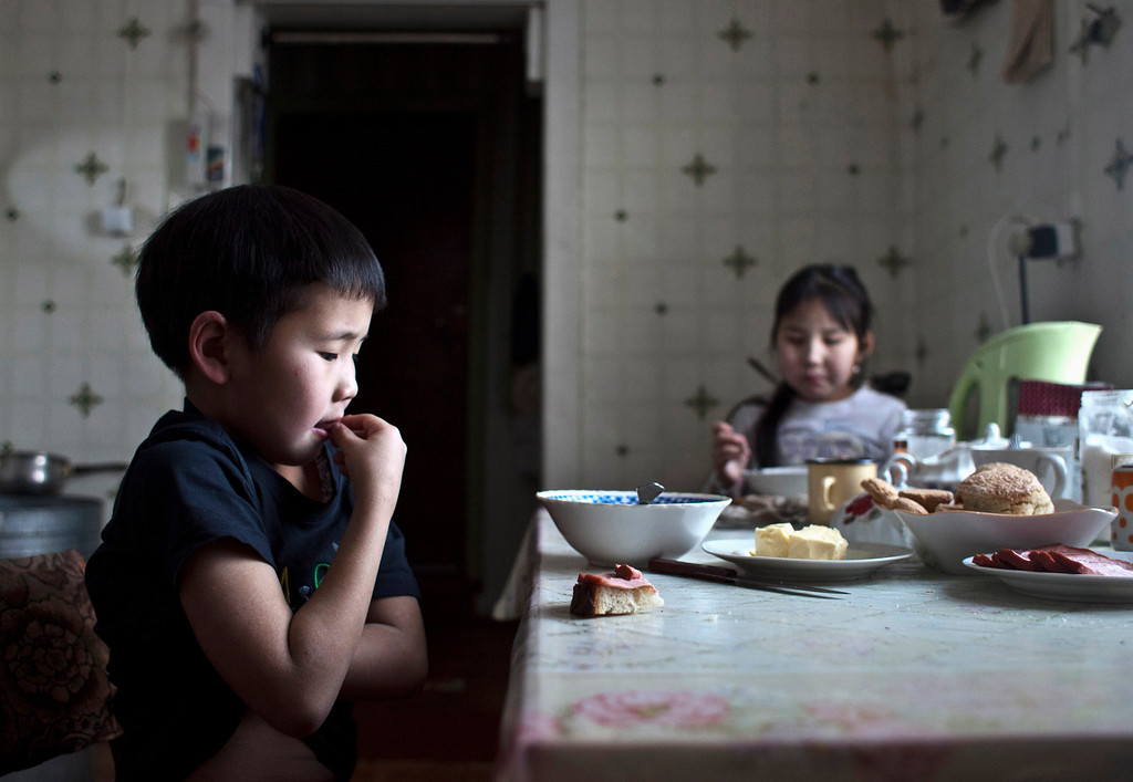 . Nikolay Vinokurov, 7, and his sister Vera Vinokurova, 9, have lunch at their grandmother\'s house in the village of Tomtor, in the Republic of Sakha, northeast Russia, January 21, 2013. The coldest temperatures in the northern hemisphere have been recorded in Sakha, the location of the Oymyakon valley, where according to the United Kingdom Met Office a temperature of -67.8 degrees Celsius (-90 degrees Fahrenheit) was registered in 1933 - the coldest on record in the northern hemisphere since the beginning of the 20th century. Yet despite the harsh climate, people live in the valley, and the area is equipped with schools, a post office, a bank, and even an airport runway (albeit open only in the summer). Picture taken January 21, 2013. REUTERS/Maxim Shemetov