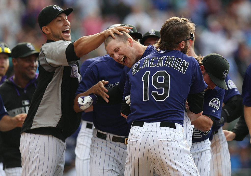 . Colorado Rockies\' Brandon Barnes, second from left, celebrates driving in the winning run with teammates, from left, Carlos Gonzalez, Charlie Blackmon and Charlie Culberson against the Los Angeles Dodgers in the 10th inning of the Rockies\' 5-4 victory in 10 innings in a baseball game in Denver on Saturday, June 7, 2014. (AP Photo/David Zalubowski)