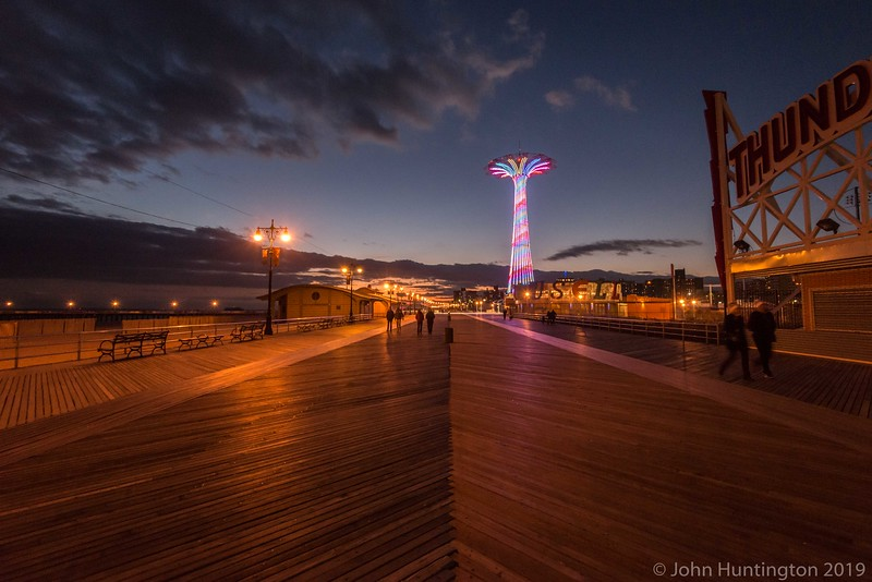 CONEY ISLAND, BROOKLYN, NY/USA -  JANUARY 1, 2016: People walk on the Coney Island boardwalk at sunset on New Years Day.