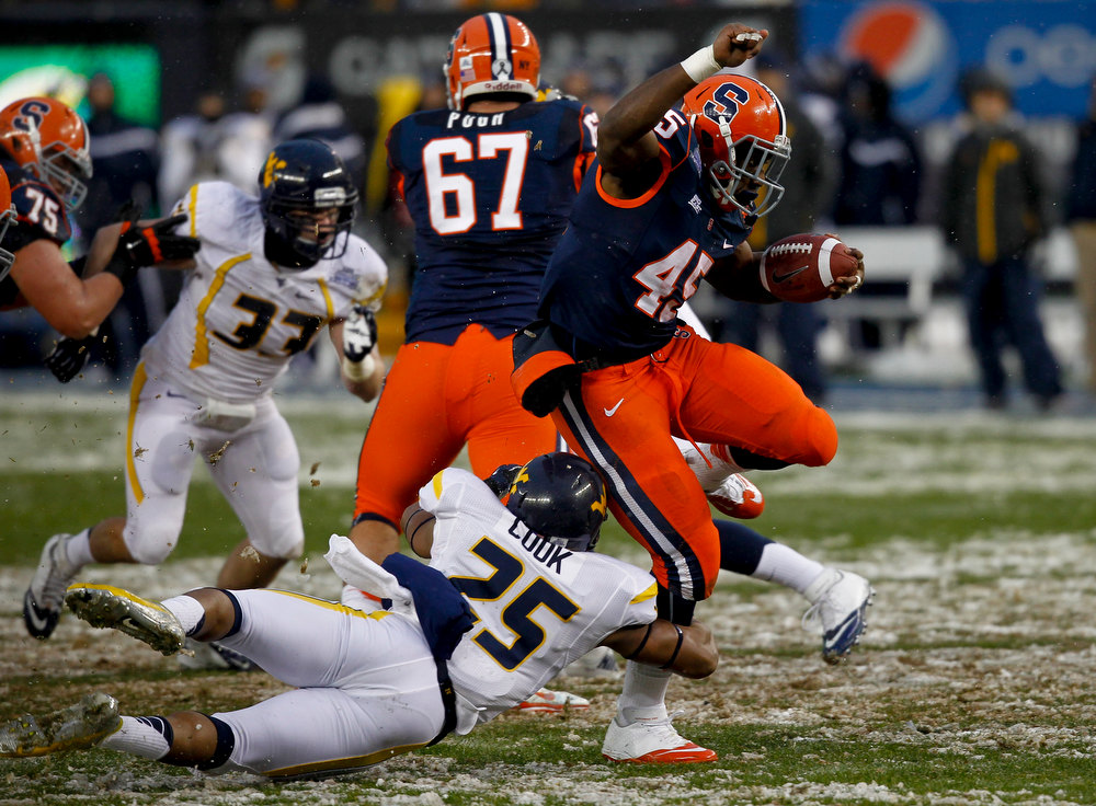 . Jerome Smith #45 of the Syracuse Orange breaks away from Darwin Cook #25 of the West Virginia Mountaineers in the New Era Pinstripe Bowl at Yankee Stadium on December 29, 2012 in the Bronx borough of New York City.  (Photo by Jeff Zelevansky/Getty Images)