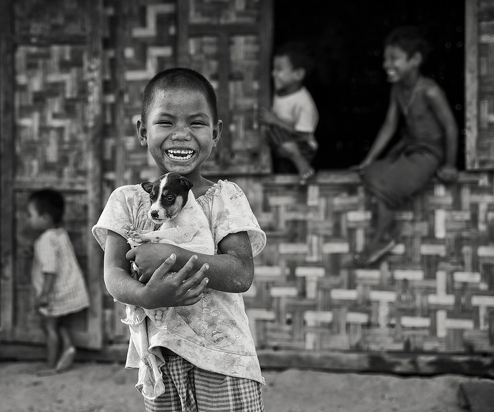 Children in a small village happy to have Christmas holiday play with their dog.  Myanmar, 2017.