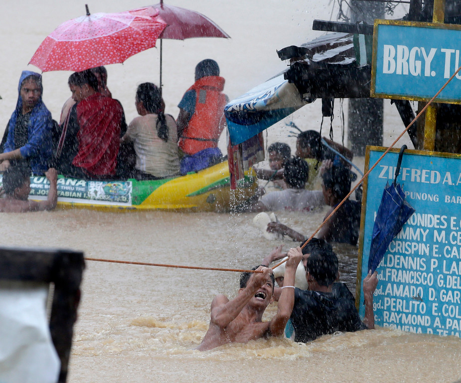 . A man clings to a rope as other rescuers use a rubber dinghy to rescue trapped residents after heavy monsoon rains spawned by tropical storm Fung-Wong flooded Marikina city, east of Manila, Philippines and most parts of  the metropolis Friday, Sept. 19, 2014. (AP Photo/Bullit Marquez)