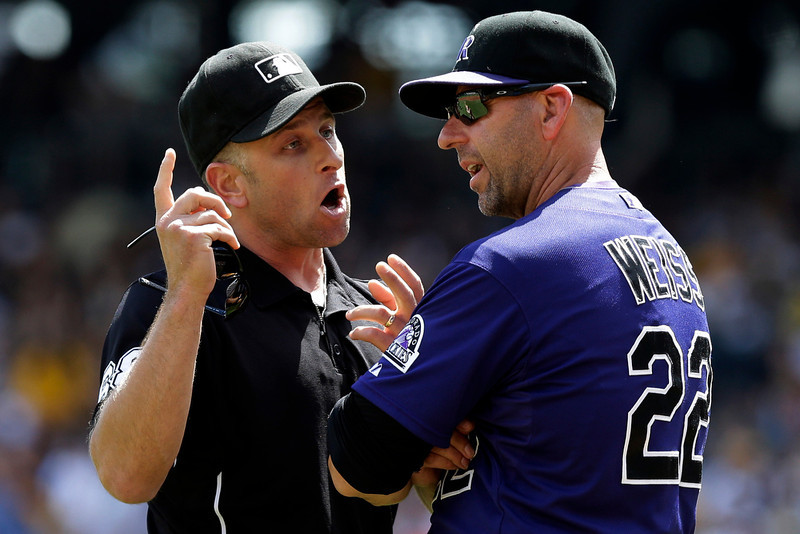 . Colorado Rockies manager Walt Weiss (22) listens as umpire Chris Guccione explains his call on a play at third base during the third inning of an MLB National league baseball game against the Pittsburgh Pirates in Pittsburgh Sunday, Aug. 4, 2013. (AP Photo/Gene J. Puskar)