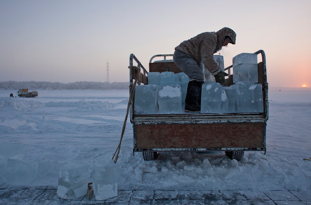 . Ruslan, 35, loads blocks of ice onto a truck outside Yakutsk in the Oymyakon valley in northeast Russia, January 17, 2013. The coldest temperatures in the northern hemisphere since the beginning of the 20th century have been recorded in the Oymyakon valley, known as the \'Pole of Cold\', where according to the United Kingdom Met Office a temperature of -67.8 degrees Celsius (-90 degrees Fahrenheit) was registered in 1933.     REUTERS/Maxim Shemetov