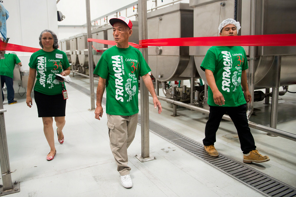 . Huy Fong CEO David Tran walks with guests during a tour at his Sriracha hot sauce factory in Irwindale on Friday, August 22, 2014. (Photo by Watchara Phomicinda/ Pasadena Star-News)