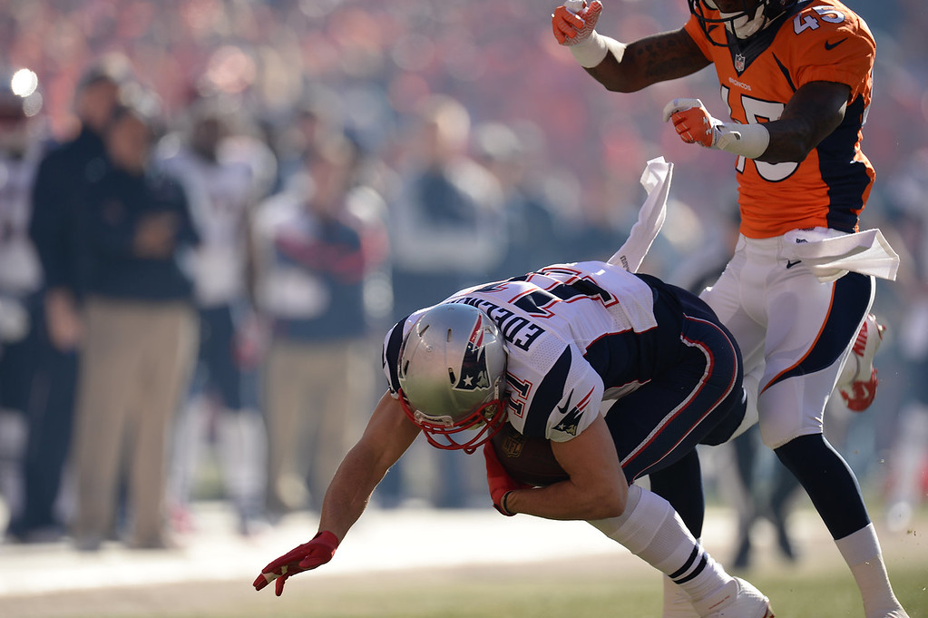 . Denver Broncos cornerback Dominique Rodgers-Cromartie (45) hits New England Patriots wide receiver Julian Edelman (11) after he makes a catch in the first quarter. The Denver Broncos take on the New England Patriots in the AFC Championship game at Sports Authority Field at Mile High in Denver on January 19, 2014. (Photo by Hyoung Chang/The Denver Post)
