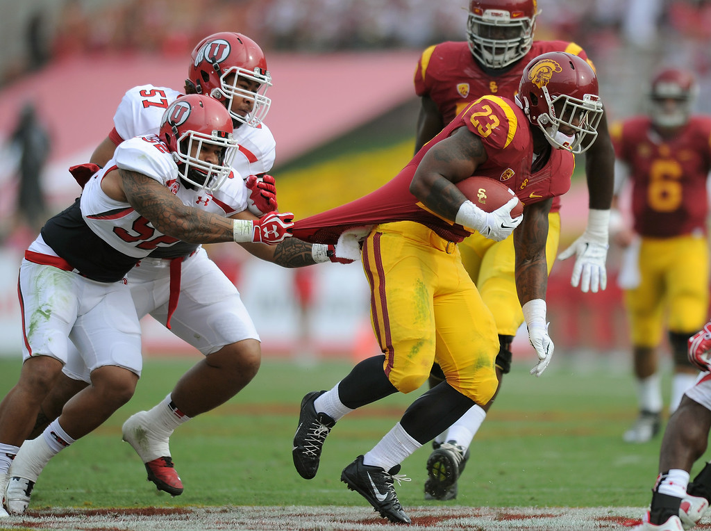 . USC\'s Tre Madden is dragged down by Utah\'s V.J. Fehoko in the third quarter, Saturday, October 26, 2013, at the L.A. Memorial Coliseum. (Michael Owen Baker/L.A. Daily News)