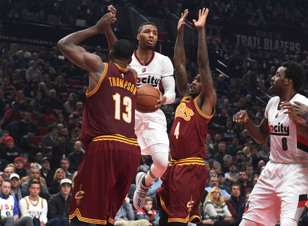 . Portland Trail Blazers guard Damian Lillard drives to the basket on Cleveland Cavaliers center Tristan Thompson and guard Iman Shumpert during the second half of an NBA basketball game in Portland, Ore., Wednesday, Jan. 11, 2017. The Blazers won 102-86. (AP Photo/Steve Dykes)