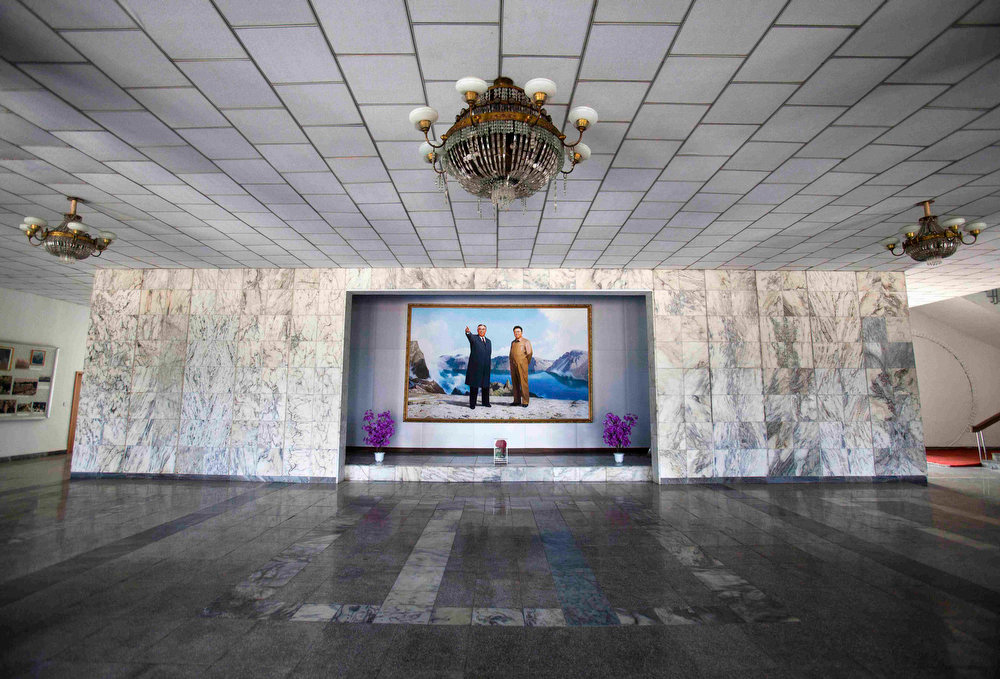 Description of . A portrait of North Korea's late leaders Kim Il Sung and Kim Jong Il hangs in a building lobby in Wason, North Korea on Oct. 6, 2011. A quasi-religious mystique surrounding the Kim family has developed over two generations, dating back to