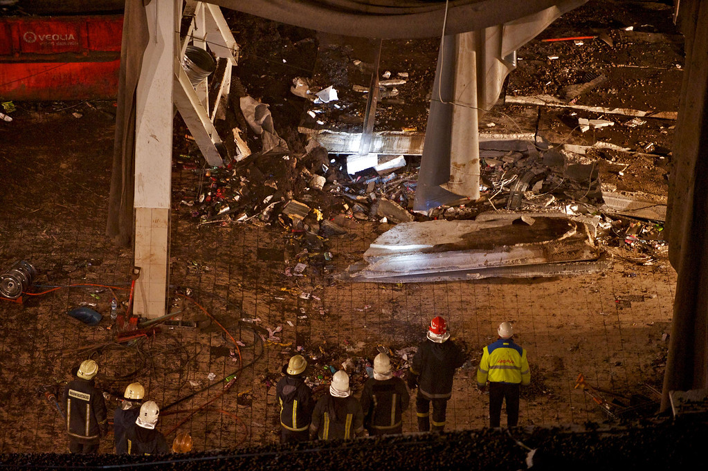 . Rescuers stand on November 23, 2013 in the Maxima supermarket in Riga, after a roof collapsed caving in on shoppers on November 21.   AFP PHOTO / ILMARS  ZNOTINS/AFP/Getty Images
