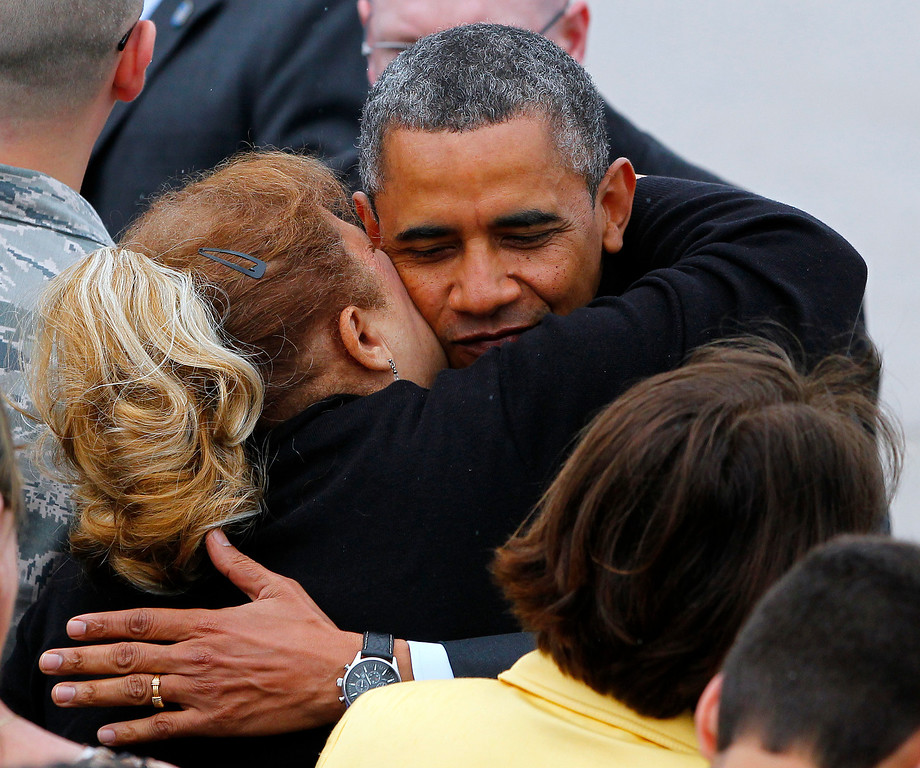 . President Barack Obama hugs a guest on the tarmac after stepping off Air Force One at McGuire Air Force Base, N.J. Tuesday, May 28, 2013.  (AP Photo/Rich Schultz)