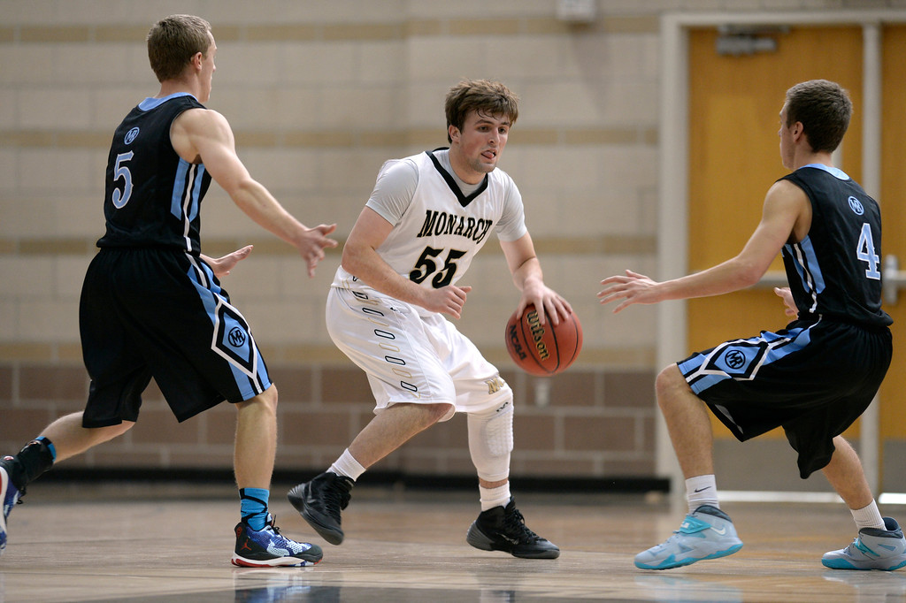 . LOUISVILLE, CO - JANUARY 3: Monarch\'s Jay MacIntyre (55) tries to move past Mountain Range\'s Grady Egan (5) and Tyler Sullivan (4). Monarch High School boys basketball takes on Mountain Range High School at Monarch High School in Louisville. (Photo by Kathryn Scott Osler/The Denver Post)