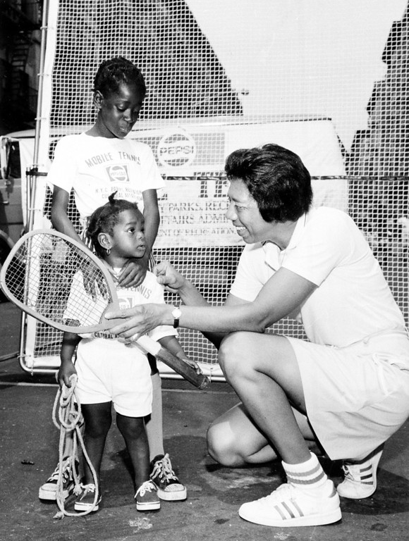 . Tennis player Althea Gibson shows the first tennis racket she used in 1942 on the streets of Harlem to Tiny Huston, 9, and her sister Monica, 1, in New York City, July 11, 1973.  Gibson opened the Pepsi-Cola summer tennis program which will bring the sport to 20,000 inner city youth.  (AP Photo)