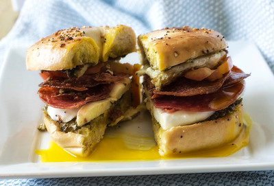 Everything Bagel - Toasted, layered with basil pesto, mozzarella, salami, Roma tomatoes and an over easy egg