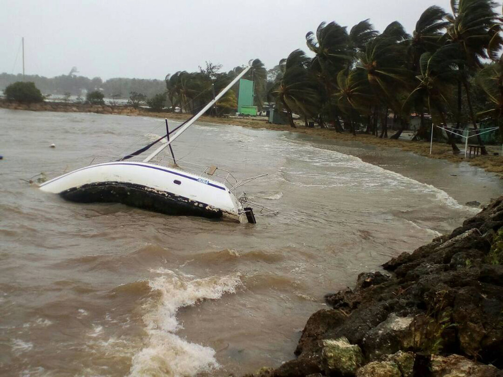 . A boat lays on its side off the shore of Sainte-Anne on the French Caribbean island of Guadeloupe, early Tuesday, Sept. 19, 2017, after the passing of Hurricane Maria. (AP Photo/Dominique Chomereau-Lamotte)