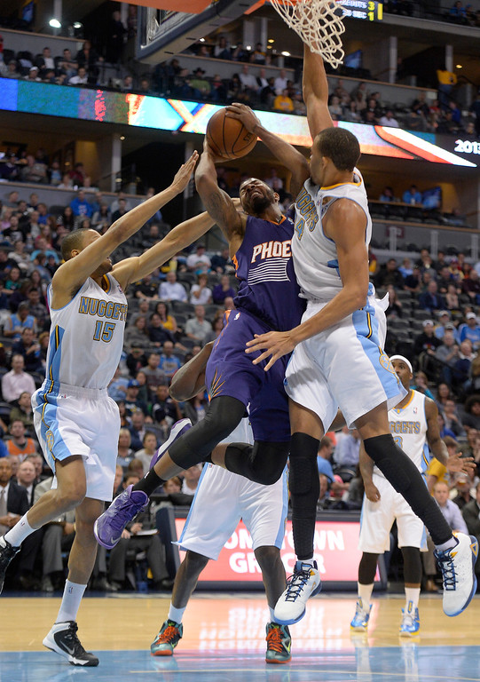 . Phoenix Suns power forward Markieff Morris (11) runs in to Denver Nuggets center JaVale McGee (34) driving to the basket during the third quarter October 23, 2013 at Pepsi Center. Morris was called for a foul on the play. (Photo By John Leyba/The Denver Post)