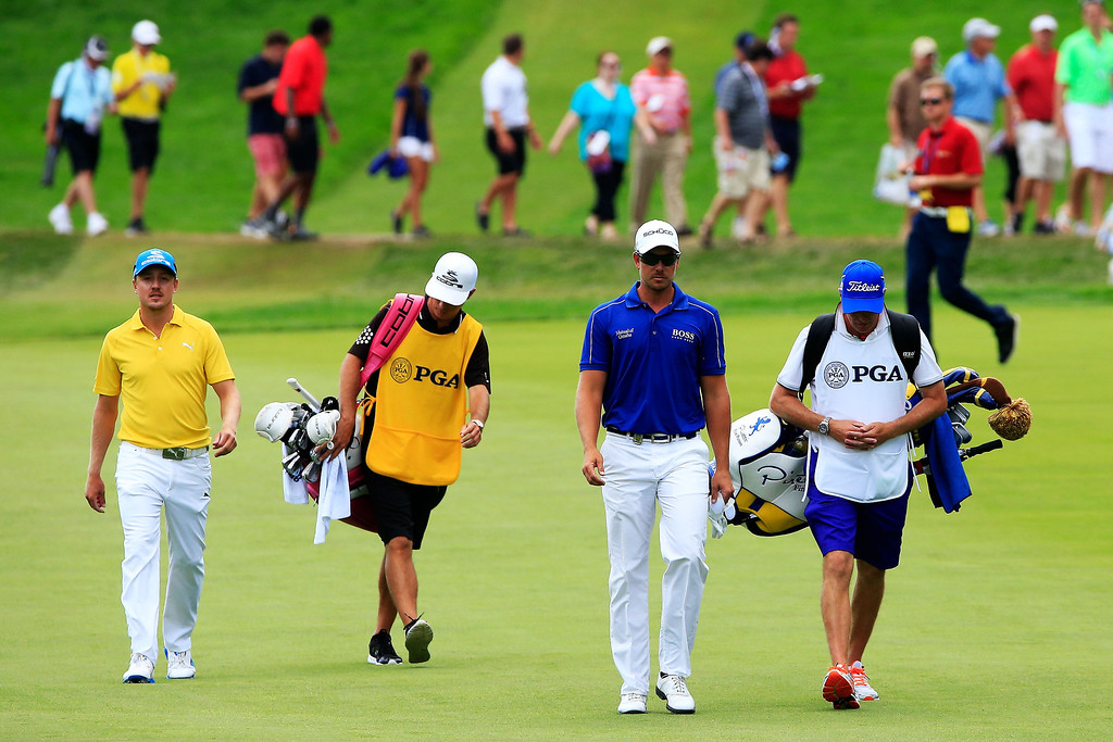 . Jonas Blixt (L) and Henrik Stenson of Sweden walk with their caddies on the first hole during the final round of the 95th PGA Championship on August 11, 2013 in Rochester, New York.  (Photo by Sam Greenwood/Getty Images)