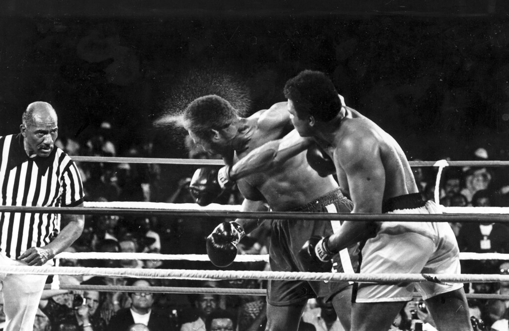 . Perspiration flies from the head of George Foreman as he takes a right from challenger Muhammad Ali in the seventh round in the match dubbed Rumble in the Jungle in Kinshasa, Zaire, Oct. 30, 1974.  Foreman was knocked out in the eighth round.  The referee, left, is Zack Clayton.  (AP Photo/Ed Kolenovsky)