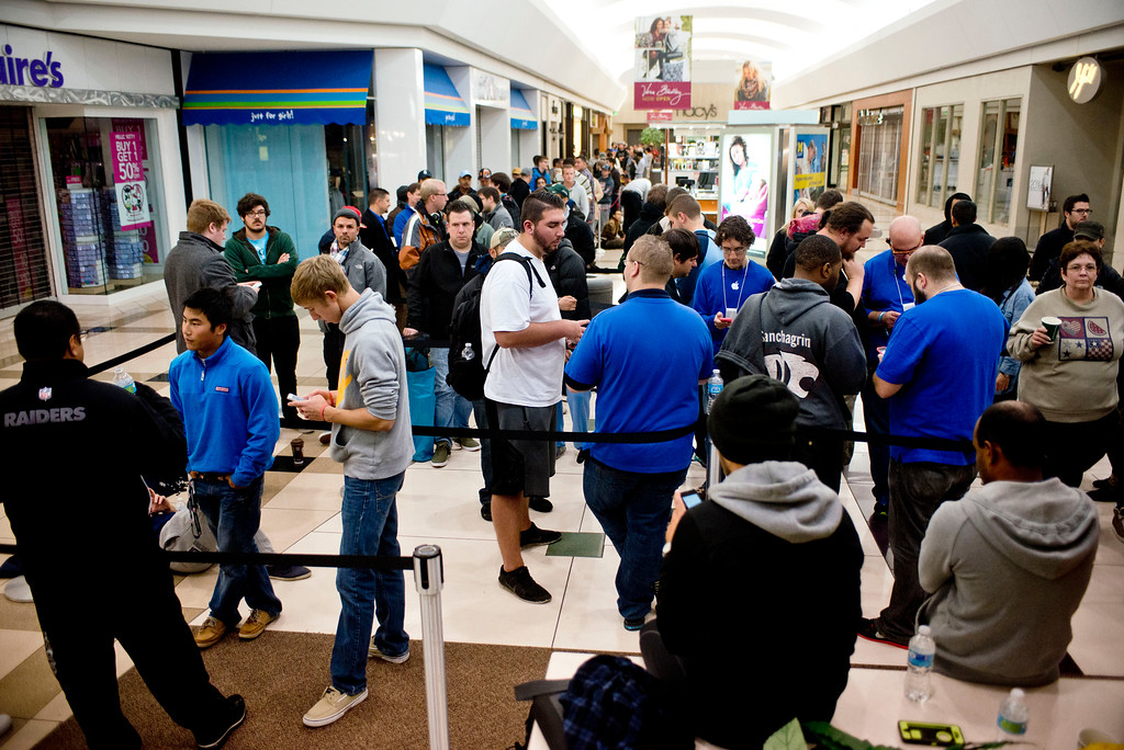 . Crowds of people wait in line for the chance to receive a brand new iPhone 6 or 6 Plus from the Apple store at  the Woodland Mall on Friday, Sept. 19, 2014 in Grand Rapids, Mich.  The highly anticipated iPhone 6 and iPhone 6 Plus are being released in stores today. (AP Photo/The Grand Rapids Press, Emily Rose Bennett)