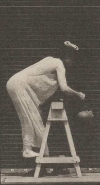 Semi-nude woman bending to fill a water jar, placing it on head