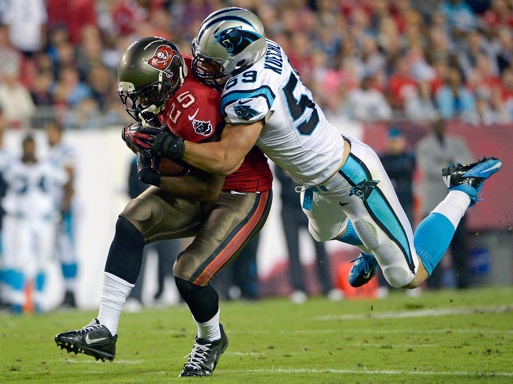 . Tampa Bay Buccaneers running back Mike James (25) catches a pass for a first down as he is tacked by Carolina Panthers middle linebacker Luke Kuechly (59) during the first half of an NFL football game in Tampa, Fla., Thursday, Oct. 24, 2013. (AP Photo/Phelan M. Ebenhack)