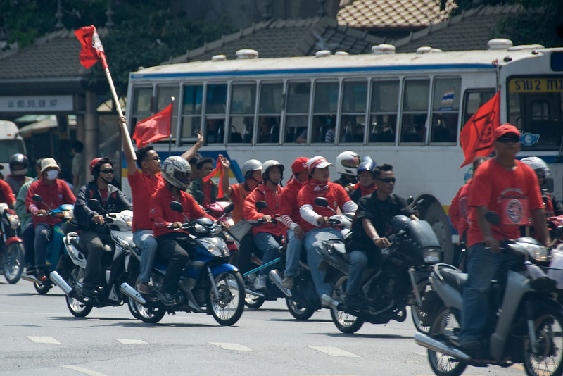 Men holding out red flags during Red Shirt Protest in Thailand
