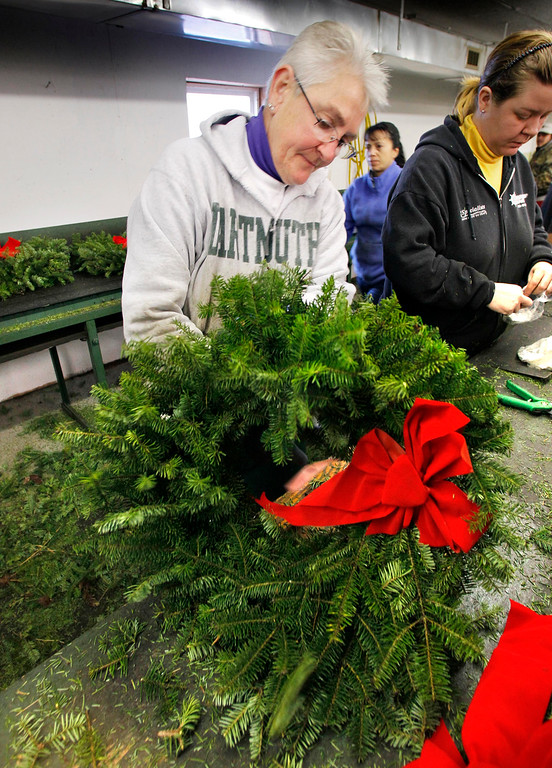 . Deb Cameron adjusts a bow on one of 200,000 wreaths destined for a veteran\'s grave site, Friday, Dec. 3, 2010, at the Worcester Wreath shop in Harrington, Maine.  A convoy of tractor trailers on the Wreaths Across America mission will leave Harrington on Sunday, Dec. 5.  The mission, which started by laying wreaths at Arlington National Cemetery 19 years ago, now sends wreaths to all 50 states. (AP Photo/Robert F. Bukaty)(AP Photo/Robert F. Bukaty)