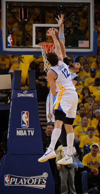 . OAKLAND, CA - APRIL 28:Andrew Bogut (12) of the Golden State Warriors goes up for a monster dunk over JaVale McGee (34) of the Denver Nuggets during the first quarter in Game 3 of the first round NBA Playoffs April 28, 2013 at Oracle Arena. (Photo By John Leyba/The Denver Post)