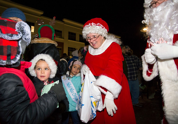 12/03/19 Wesley Bunnell | StaffrrThe 68th annual Bristol Carol Sing and 29th annual Tree Lighting presented by Webster Bank and the Central CT Chambers of Commerce took place on Tuesday night outside to Webster Bank at 150 Main St. Ms. Clause hands a candy cane to Luke Hull, L, age 8, and brother Matthew Hull, age 6.