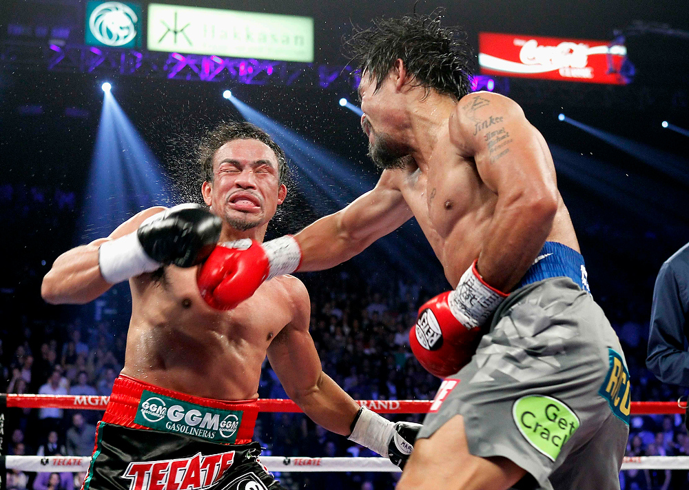 . Juan Manuel Marquez, left, of Mexico takes a punch from Manny Pacquiao of the Philippines during their welterweight fight at the MGM Grand Garden Arena in Las Vegas, Nevada December 8, 2012. Marquez went on to win with a sixth-round knockout. REUTERS/Steve Marcus