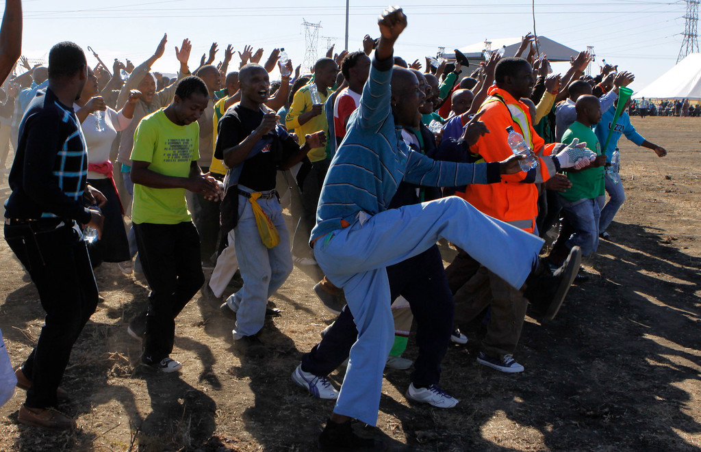 . Miners arrive for a commemoration service for the striking platinum miners that were killed a year ago, in Marikana, South Africa, Friday Aug. 16, 2013.  It was a hot dusty afternoon at the brown rock hills near South Africaís Lonmin PLC mine in Marikana when South Africa was forced to face another bloody event in its long history of apartheid and state violence. Police opened fire a year ago on striking miners who carried sticks and homemade spears, killing 34. The details of Aug. 16, 2012 are still unsettled a year later in the small, impoverished community of Marikana, in South Africa\'s mineral-rich northwest.  (AP Photo/Denis Farrell)