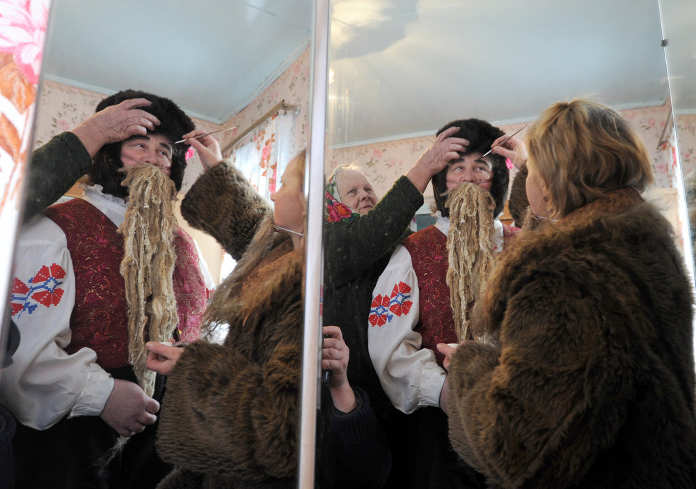. A picture taken through mirrors shows a woman applying make-up on a man wearing a costume, during a Christmas celebration in the town of Richev, some 290 km south from Minsk, on January 7, 2013. Orthodox Christians celebrate Christmas on January 7 in the Middle East, Russia and other Orthodox churches that use the old Julian calendar instead of the 17th-century Gregorian calendar adopted by Catholics, Protestants, Greek Orthodox and commonly used  attendsin secular life around the world.   AFP PHOTO / VIKTOR  DRACHEV/AFP/Getty Images