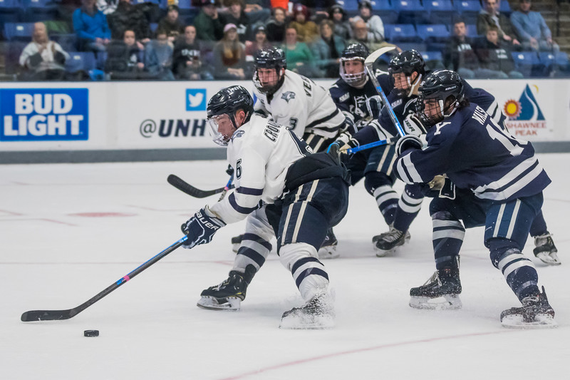 UNH's Angus Crookshank (6) takes a shot while being defended by Yale's Anthony Walsh (16) during hockey action in Durham Saturday. [Scott Patterson/ Fosters.com]