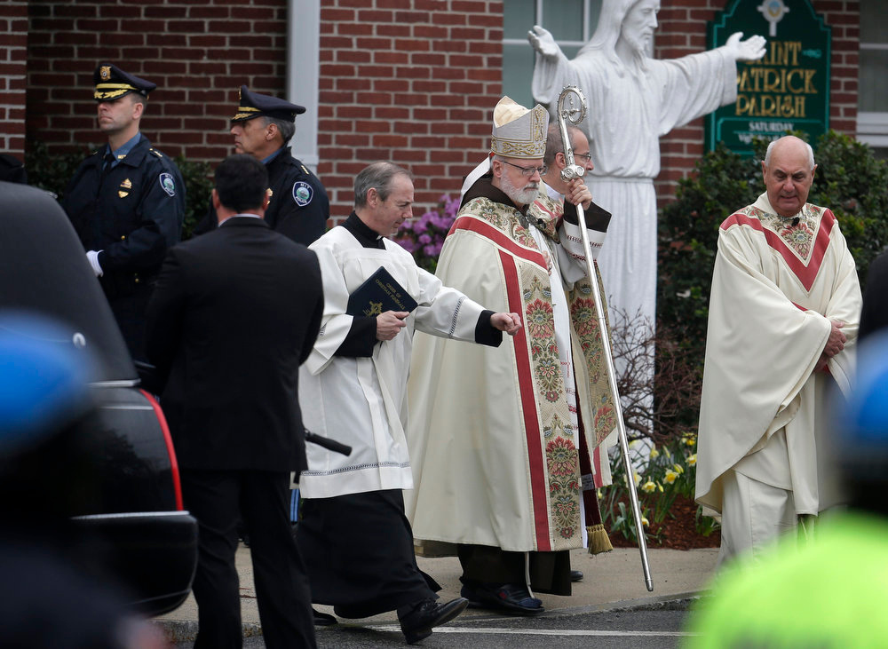 Description of . Boston Archbishop Cardinal Sean O'Malley, center, departs St. Patrick's Church in Stoneham, Mass., with other members of the clergy following a funeral Mass for Massachusetts Institute of Technology police officer Sean Collier, Tuesday, April 23, 2013. Collier was fatally shot on the MIT campus Thursday, April 18, 2013. Authorities allege that the Boston Marathon bombing suspects were responsible. (AP Photo/Steven Senne)