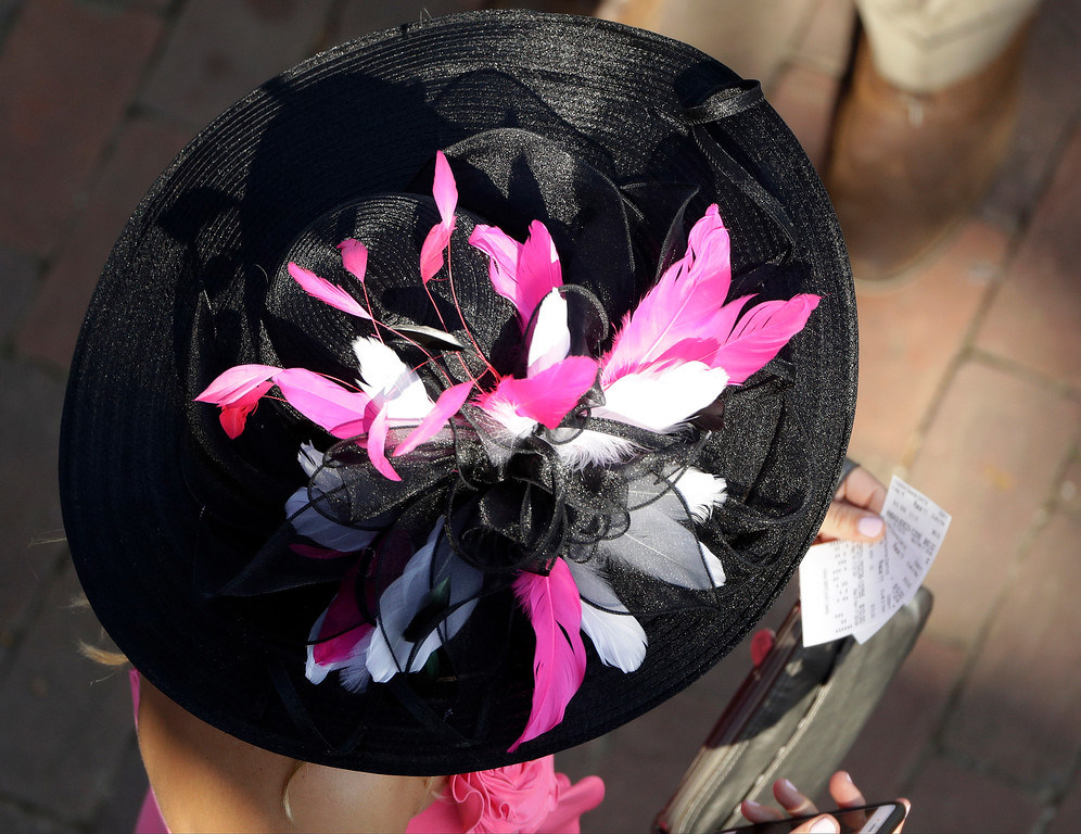 . A fan looks at her bets before the 142nd running of the Kentucky Derby horse race at Churchill Downs Saturday, May 7, 2016, in Louisville, Ky. (AP Photo/Charlie Riedel)