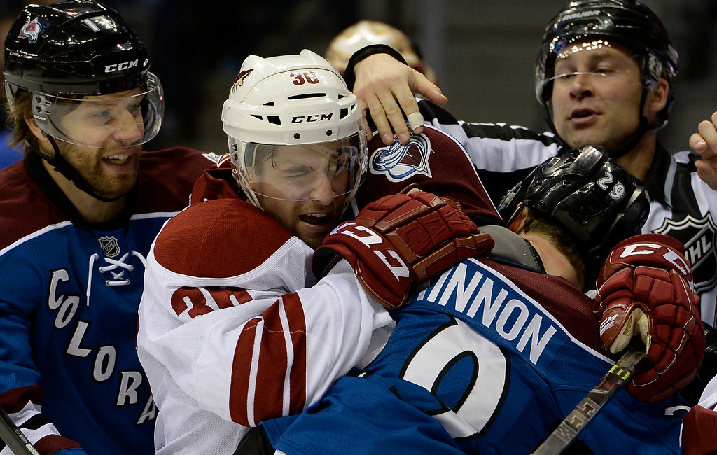 . DENVER, CO - FEBRUARY 16: Arizona Coyotes right wing Mark Arcobello (36) grabs a hold of Colorado Avalanche center Nathan MacKinnon (29) in front of the goal during the third period February 16, 2015 at Pepsi Center. (Photo By John Leyba/The Denver Post)