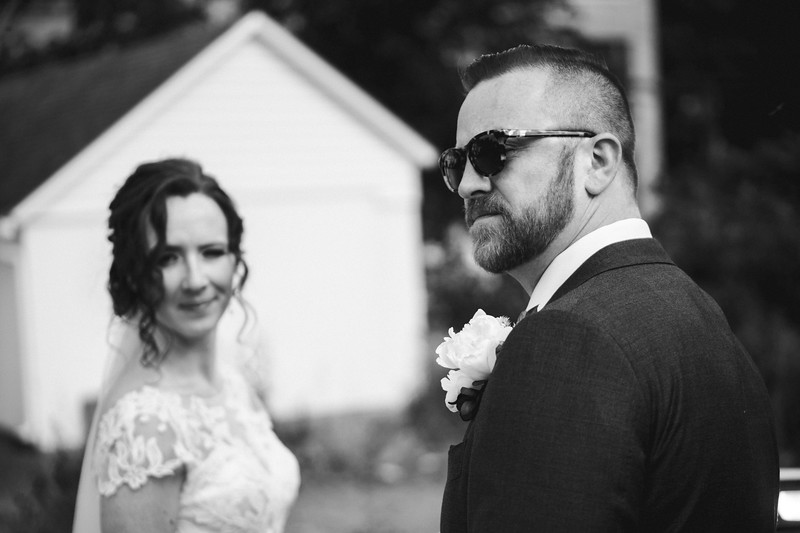 The groom, wearing sunglasses, looks over his shoulder as the bride smirks into the camera from the background.