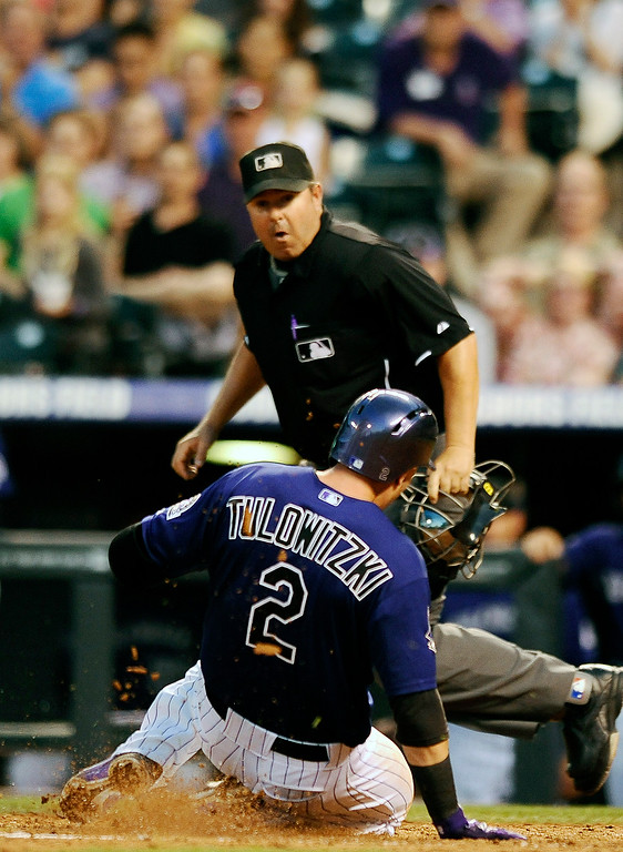 . Colorado Rockies\' Troy Tulowitzki (2) slides safely into home plate to score in the fourth inning of a baseball game against the Milwaukee Brewers, Friday, July 26, 2013, in Denver. (AP Photo/Chris Schneider)